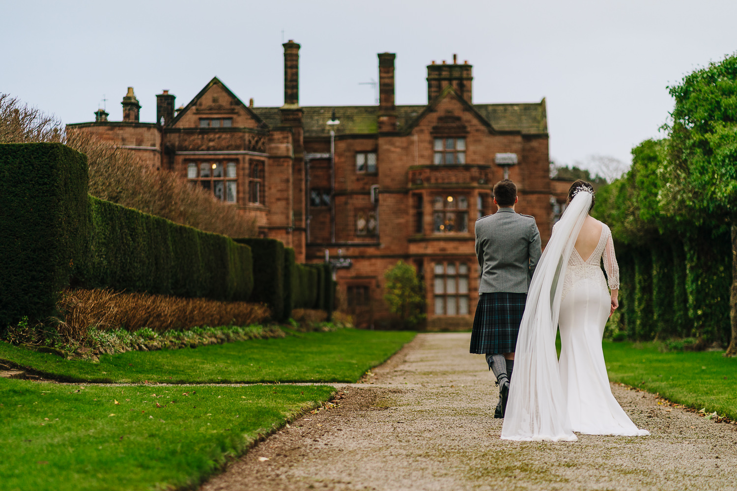 Bride and groom walking towards Thornton Manor