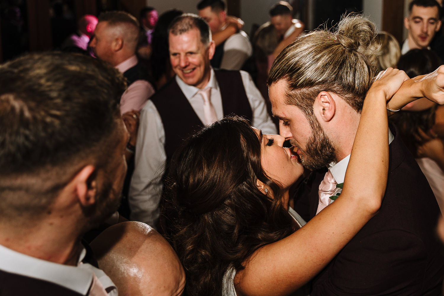Bride and groom kissing on a packed dance floor