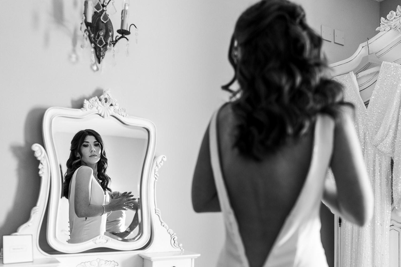 bride in her dress looking in the mirror