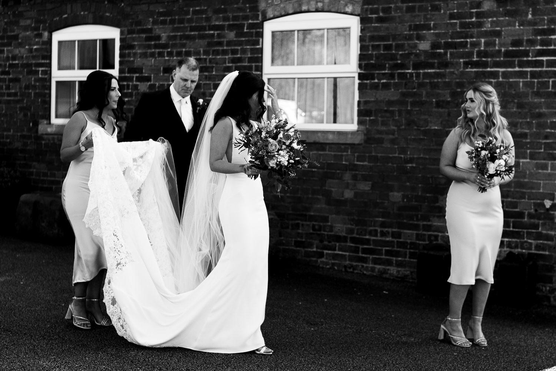 bride walking to the ceremony at Sandhole Oak Barn