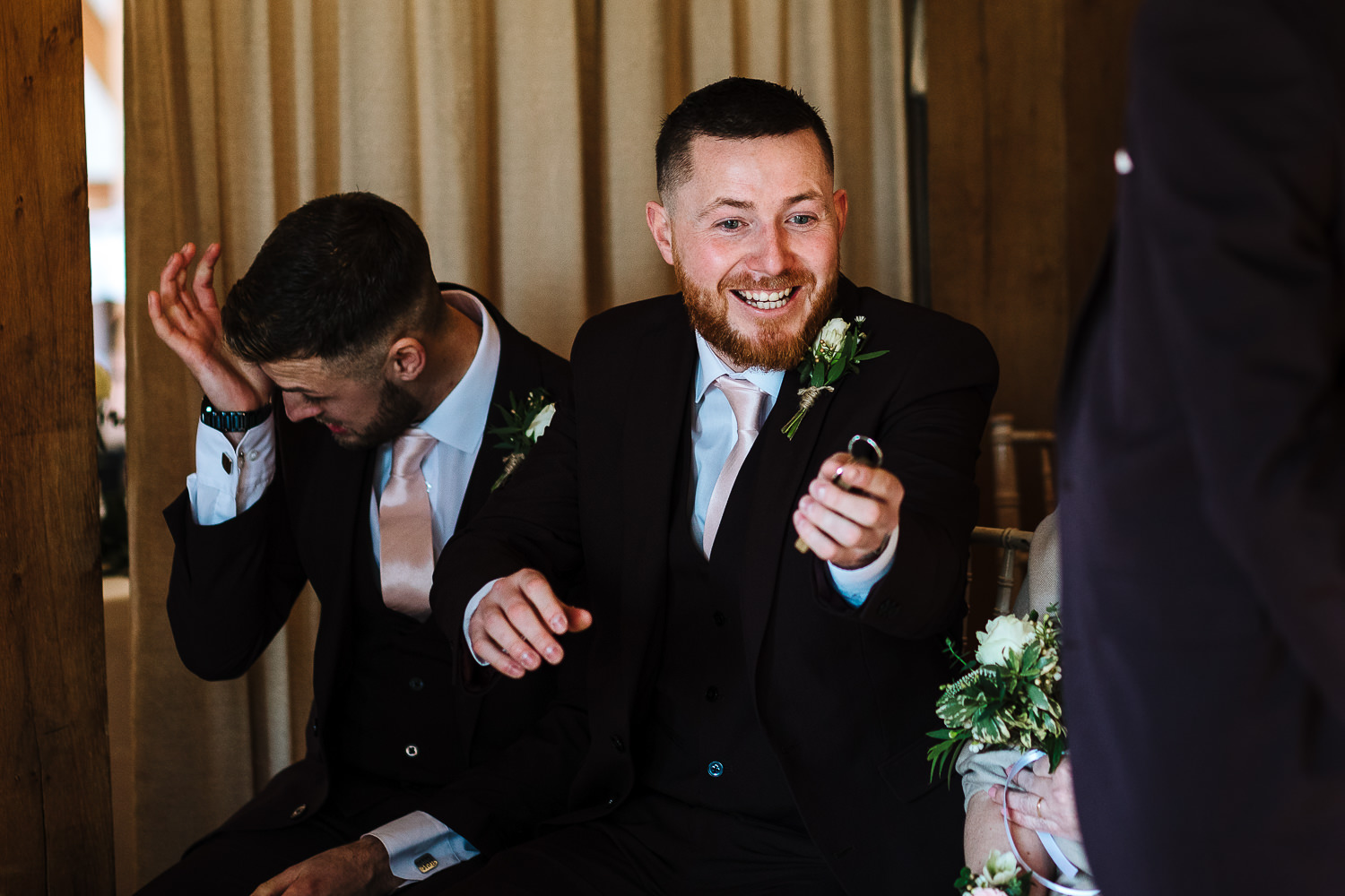 Groomsmen laughing in the ceremony room