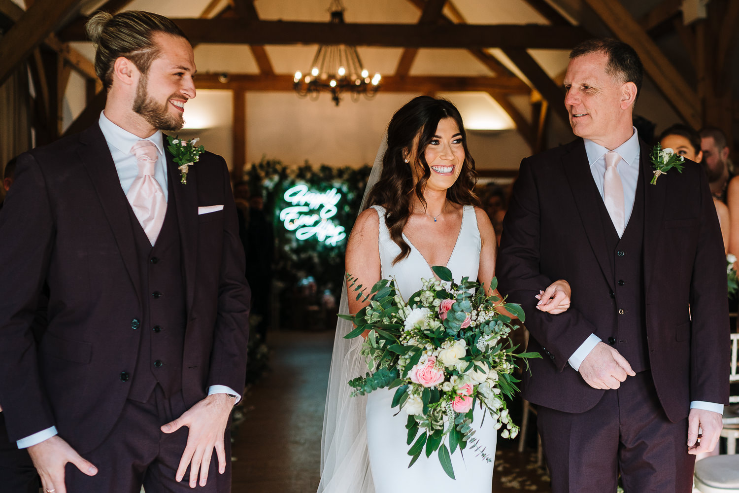 bride laughing with the groom and her dad