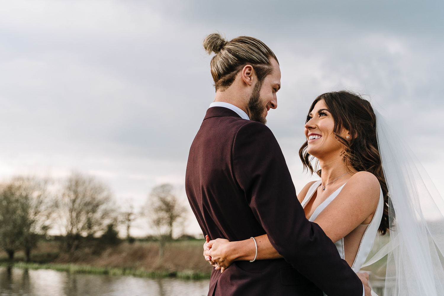 A photo of the bride and groom by the lake in lovely light