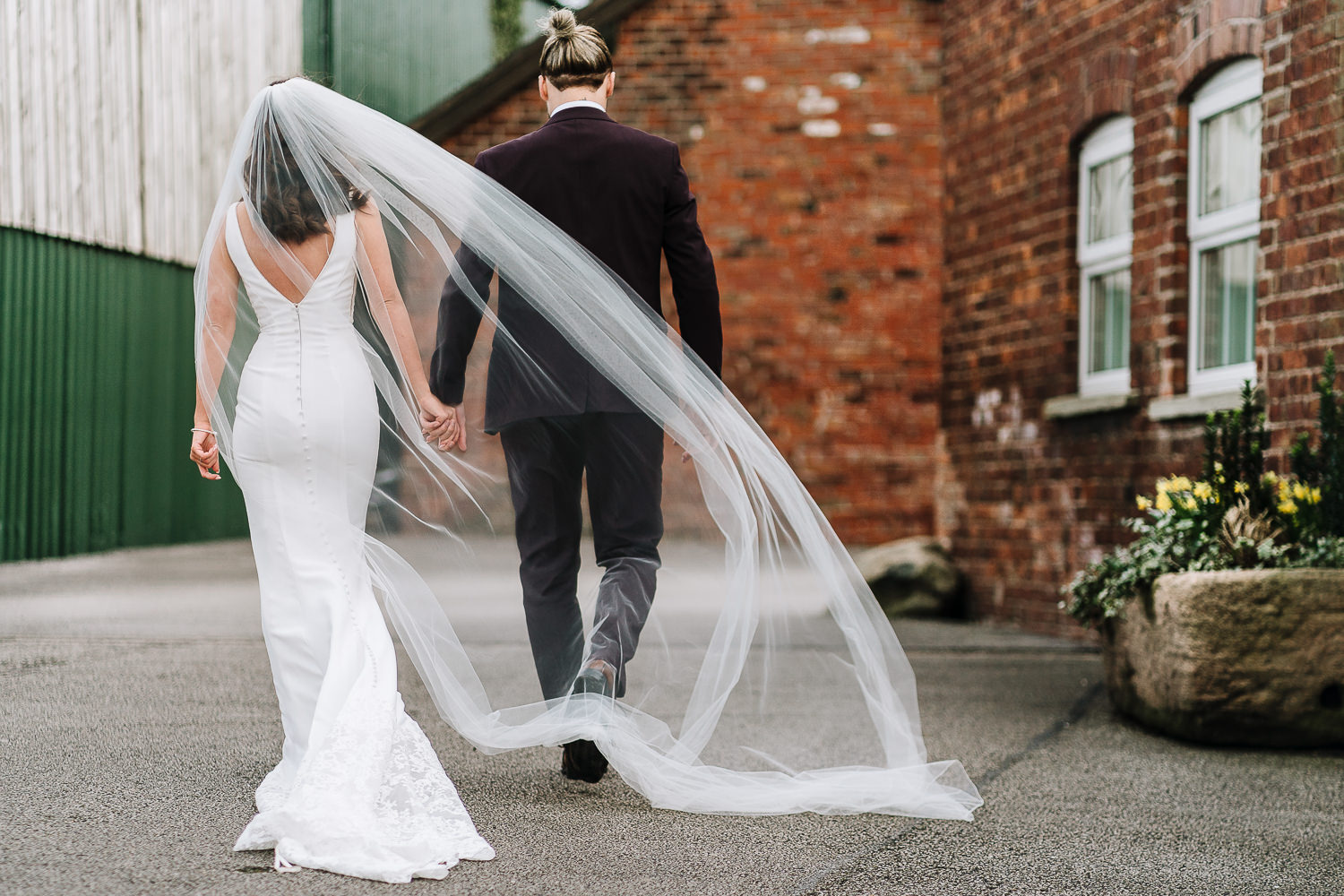 bride and groom walking with the veil blowing in the air