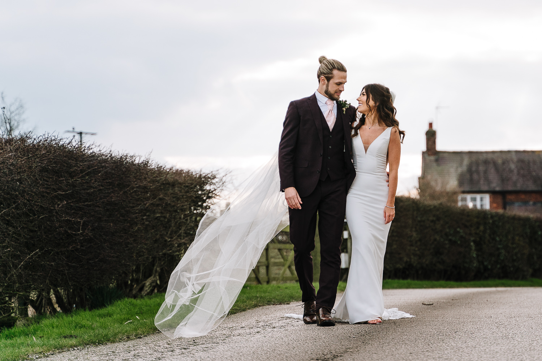 bride and groom walking down the drive at Sandhole oak Barn