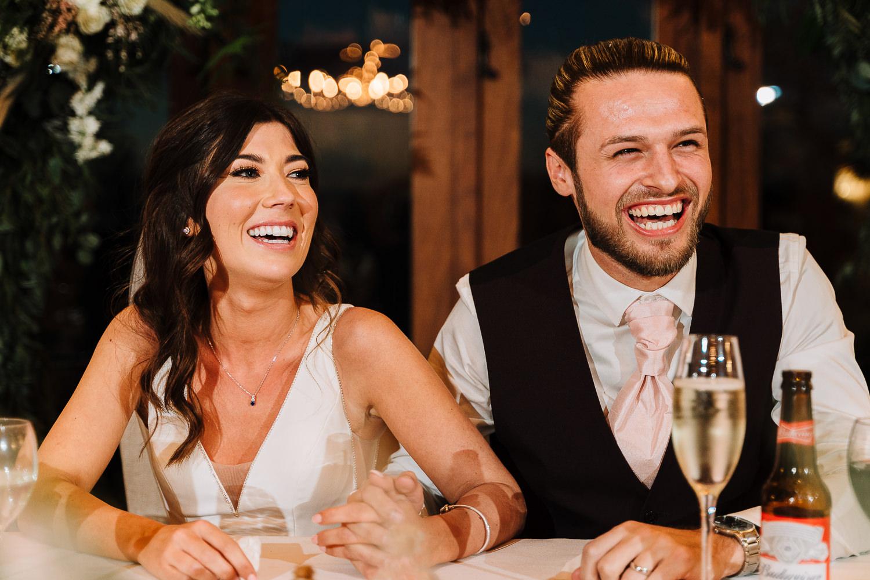Bride and groom laughing at Sandhole Oak Barn