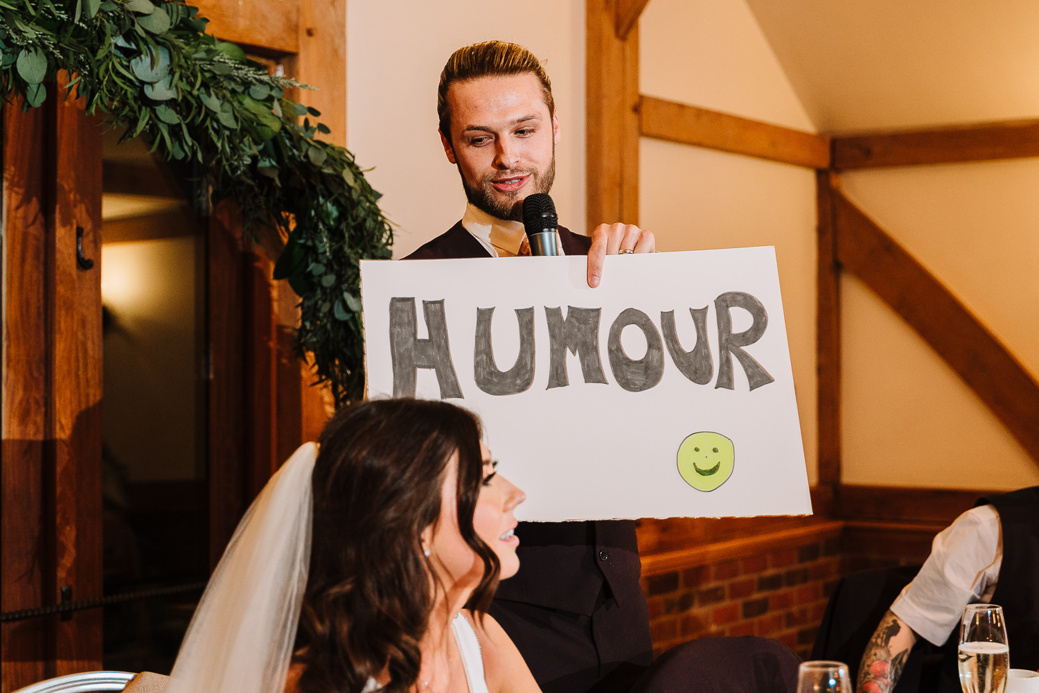 Groom holding up a humour sign