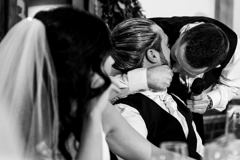 Best man kissing the groom