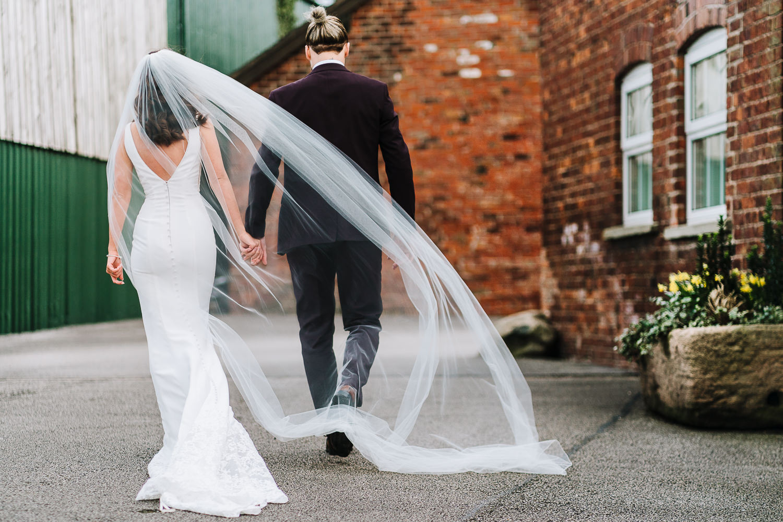 Bride and groom walking through Sandhole Oak Barn