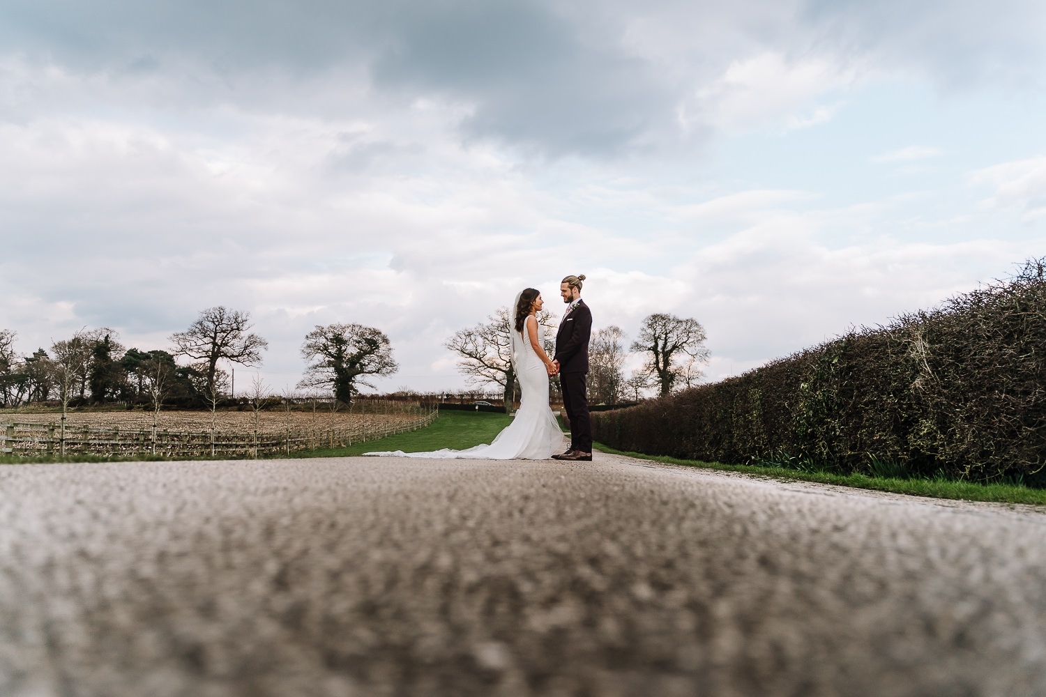 Portrait of the bride and groom on the long drive at Sandhole Oak Barn