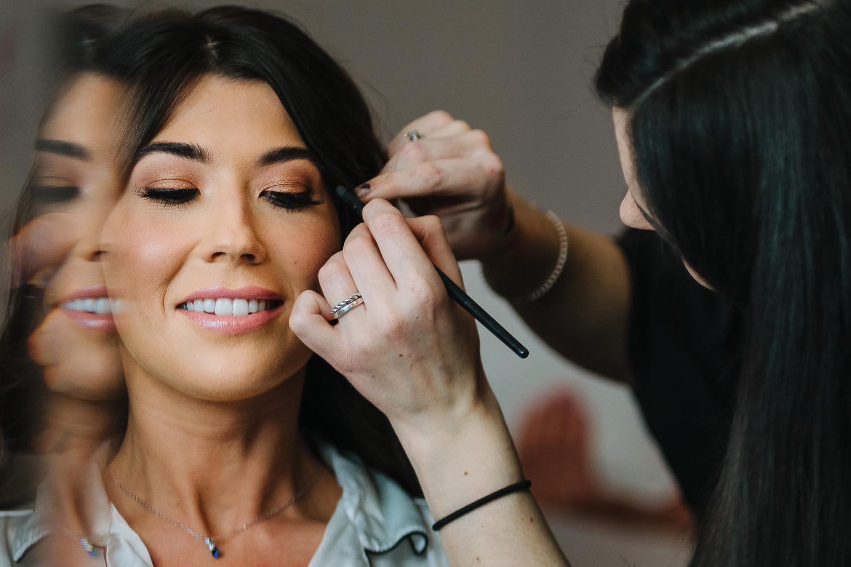 Bride having her make up done at Sandhole Oak Barn