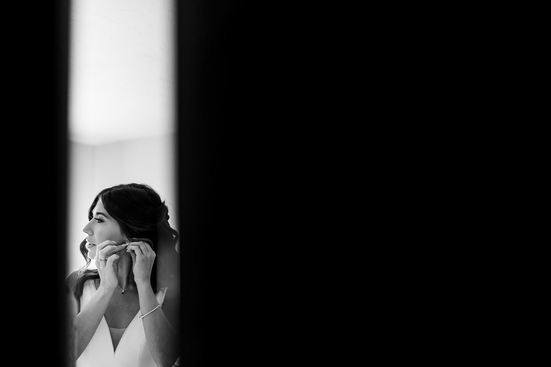 Bride putting her earrings in at Sandhole Oak Barn