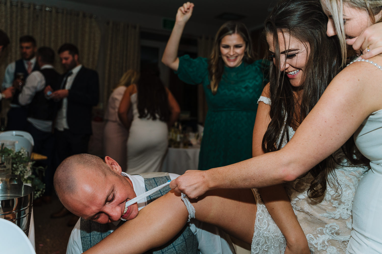 Groom biting part of brides dress