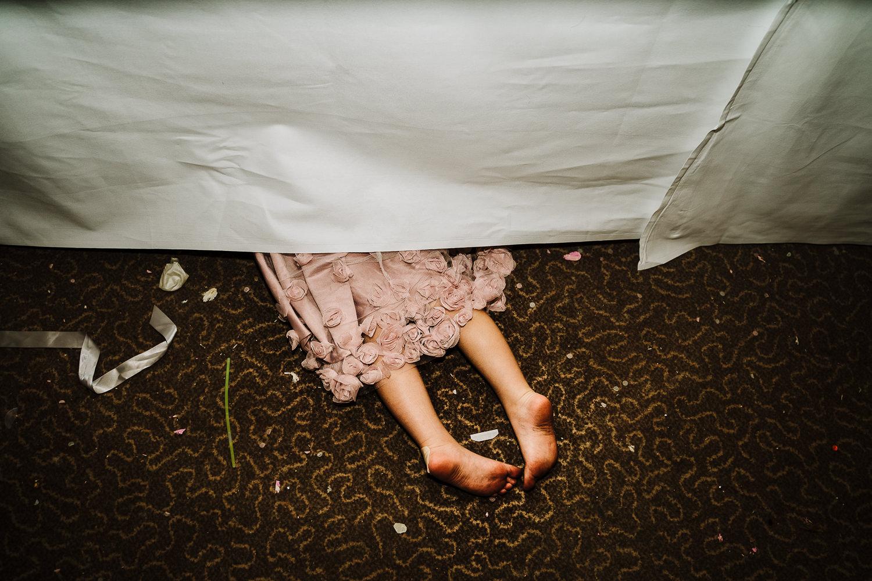 flower girl hiding under table