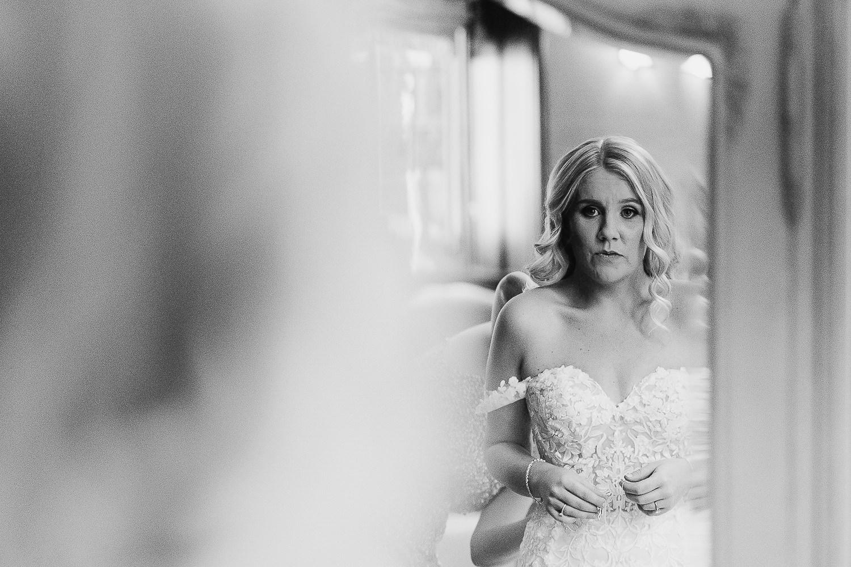 Bride looking in the mirror at Falcon Manor