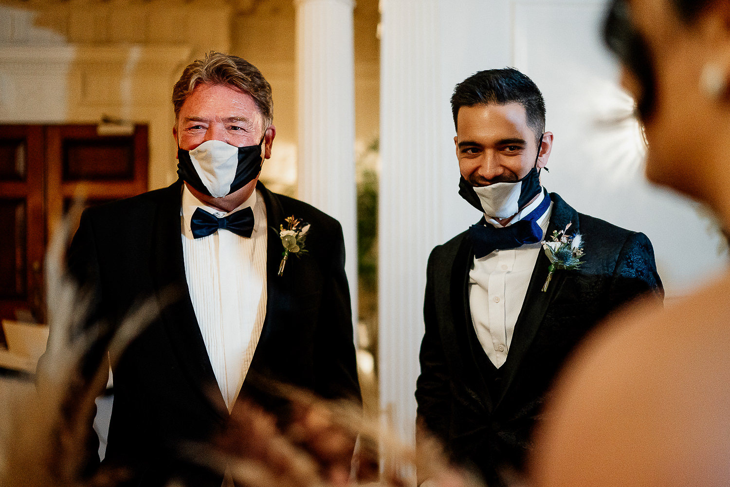 Groom and his dad laughing in face masks