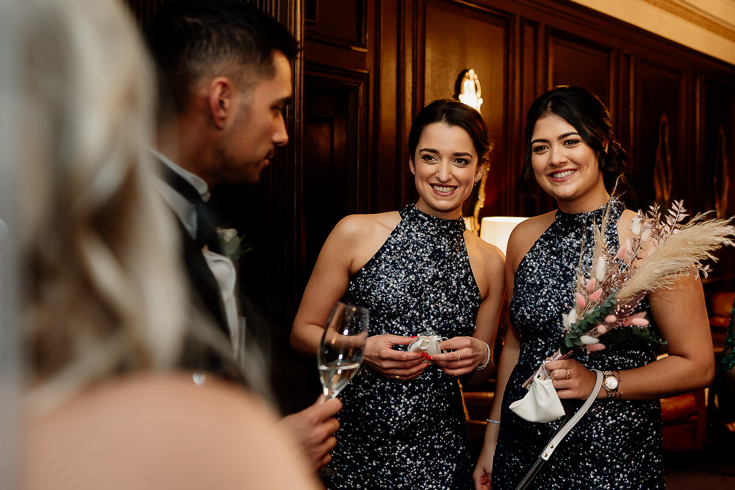 Bridesmaids smiling at the couple
