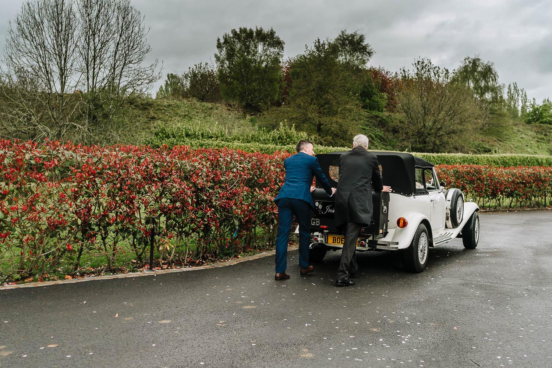 Groom pushing a broken down wedding car