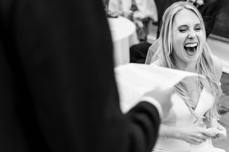 Bride laughing during groom speech