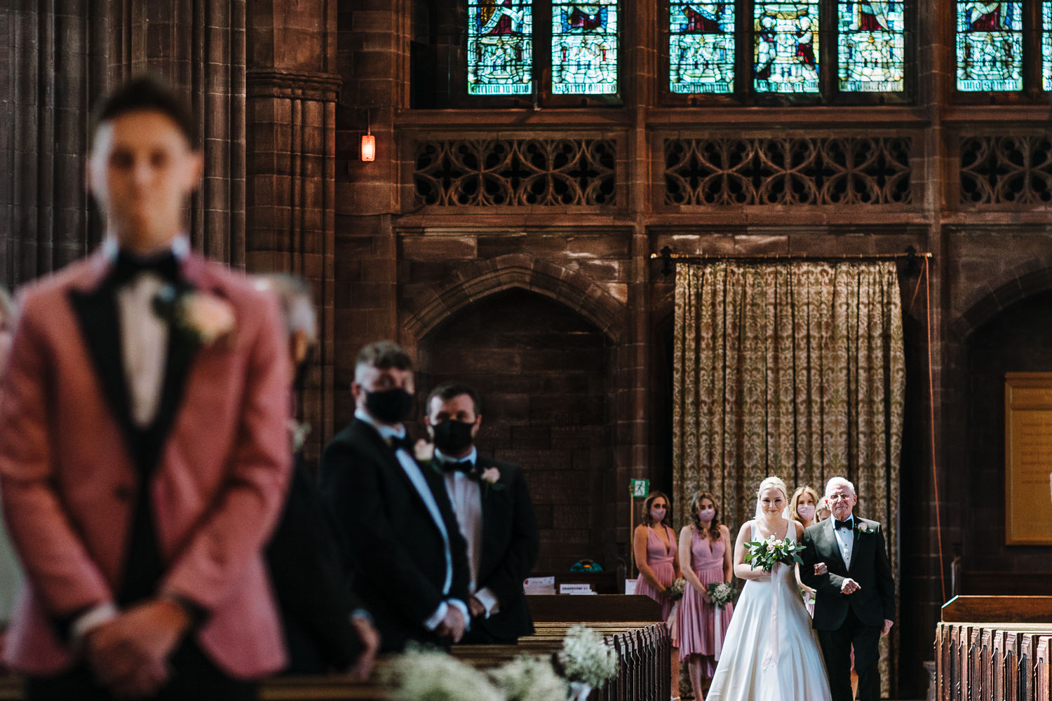 bride walking into church and groom crying