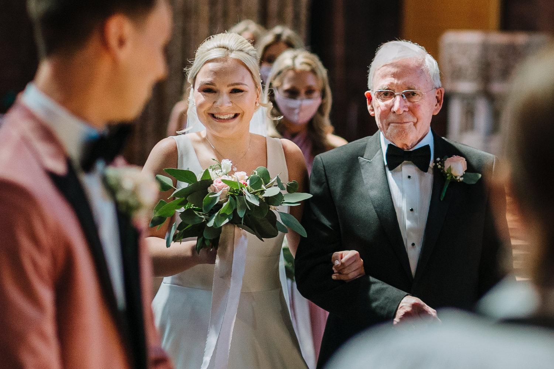 bride walking into church with granddad