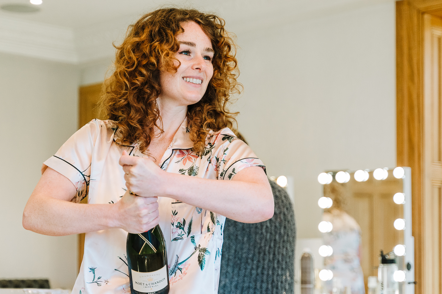 Bridesmaid opening a bottle of champagne at Merrydale Manor