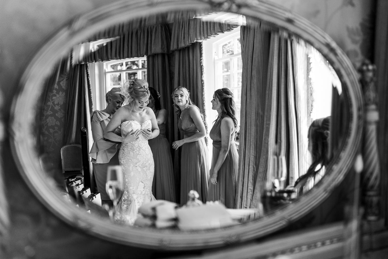 Bride putting on her dress at Delamere Manor