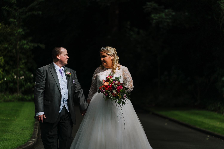 Bride and groom walking and smiling at Samlesbury Hall