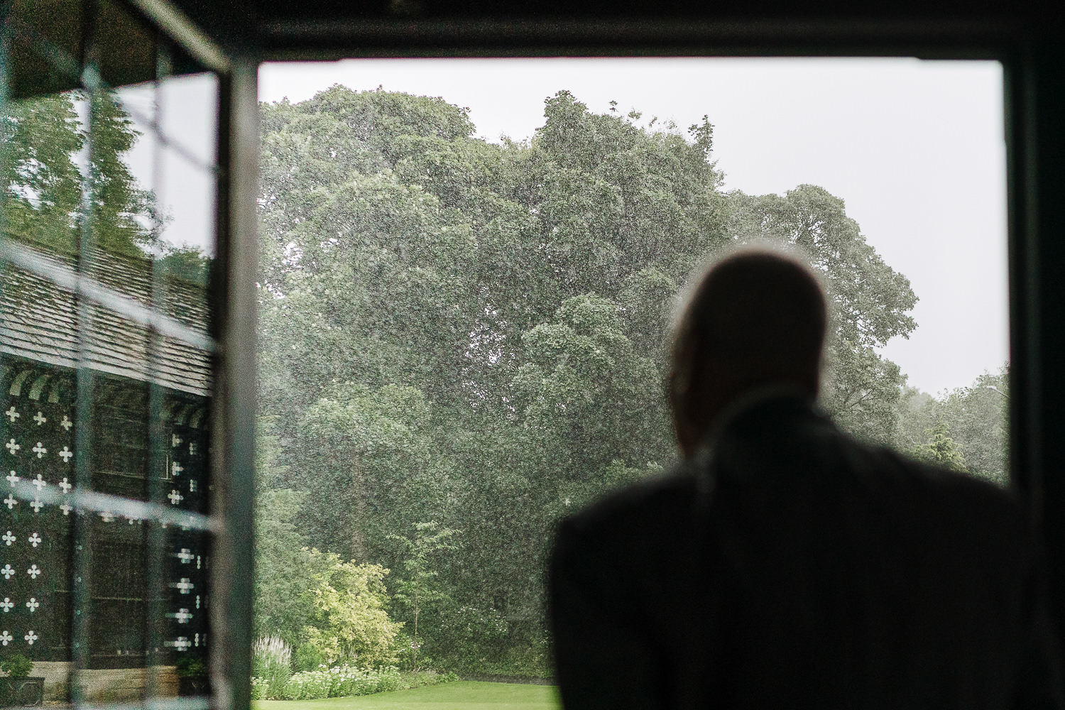 Wedding guest looking out at the rain
